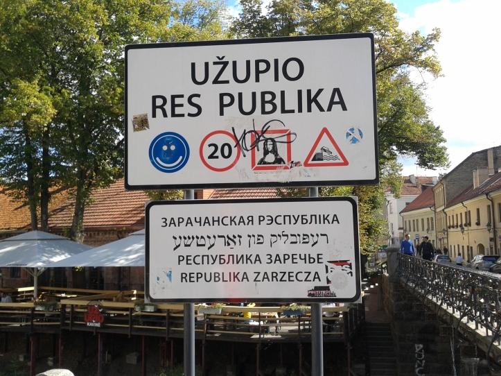 Placa na entrada à República Uzupio com alguns alertas, como a obrigação de sorrir, a velocidade máxima para carros (20km/h) e o do perigo de cair no rio com o carro